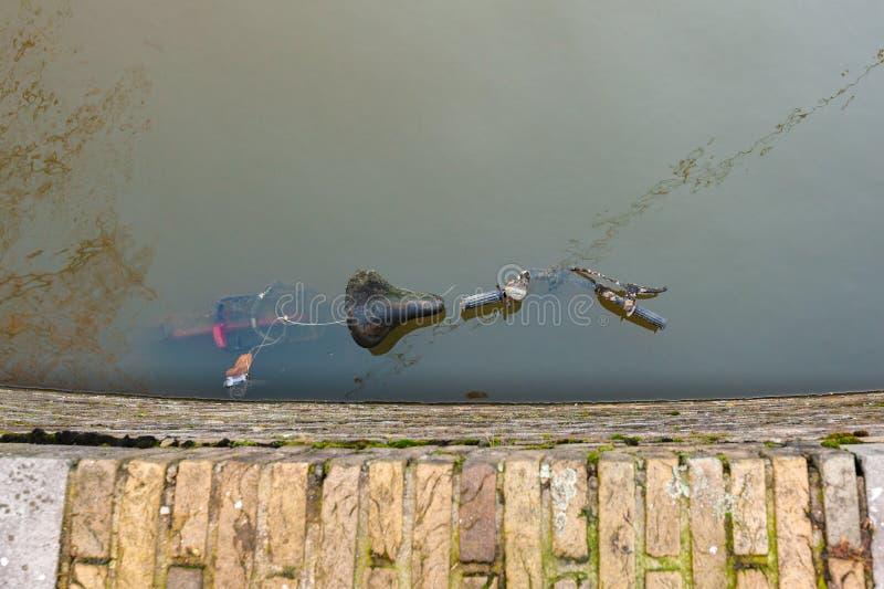 La bicyclette s'est garée dans l'eau sur le quai d'un canal à Delft photos stock