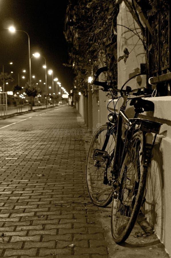 La bicyclette se tient à la barrière la nuit photos stock