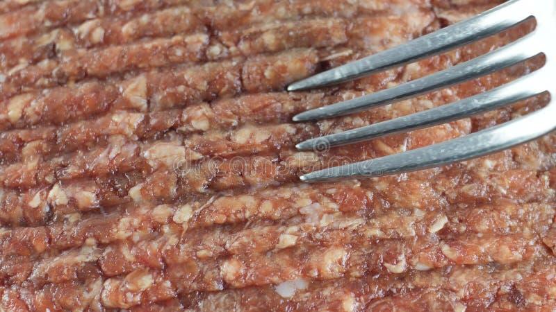 La bifurcación pasa en la carne picadita del pollo crudo, opinión de top del tiro del primer fotografía de archivo