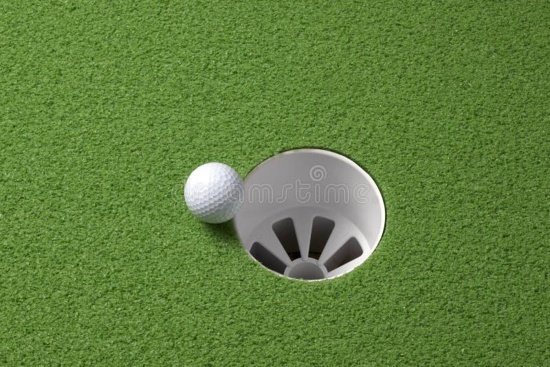La bille de golf roule pour trouer photo libre de droits