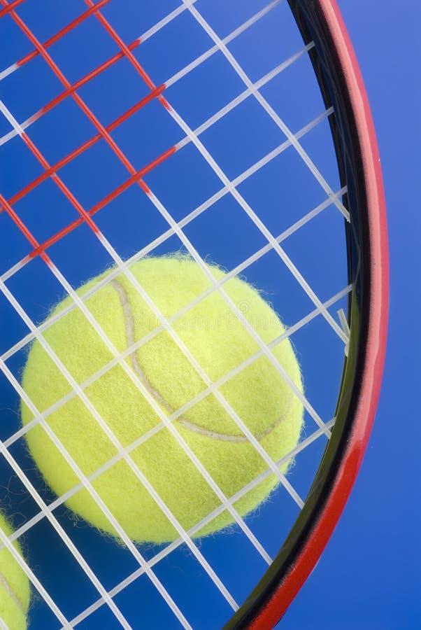 La bille de tennis est sous une pièce d'une raquette de tennis images libres de droits
