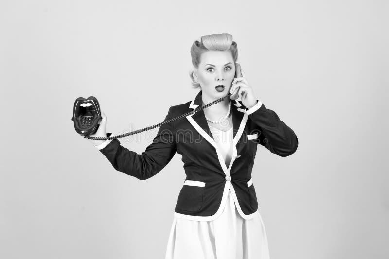 La bionda arriccia la ragazza nello stile d'annata che chiama con le labbra del cavo telefona nel fondo posteriore e bianco fotografia stock libera da diritti