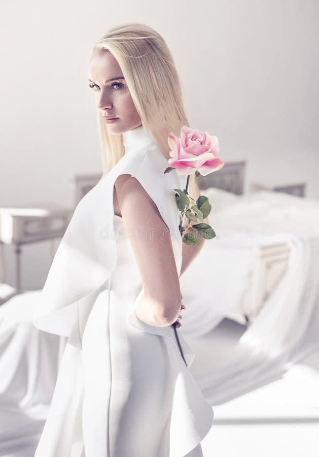 La bionda elegante e giovane che tiene un bello rosa è aumentato fotografia stock