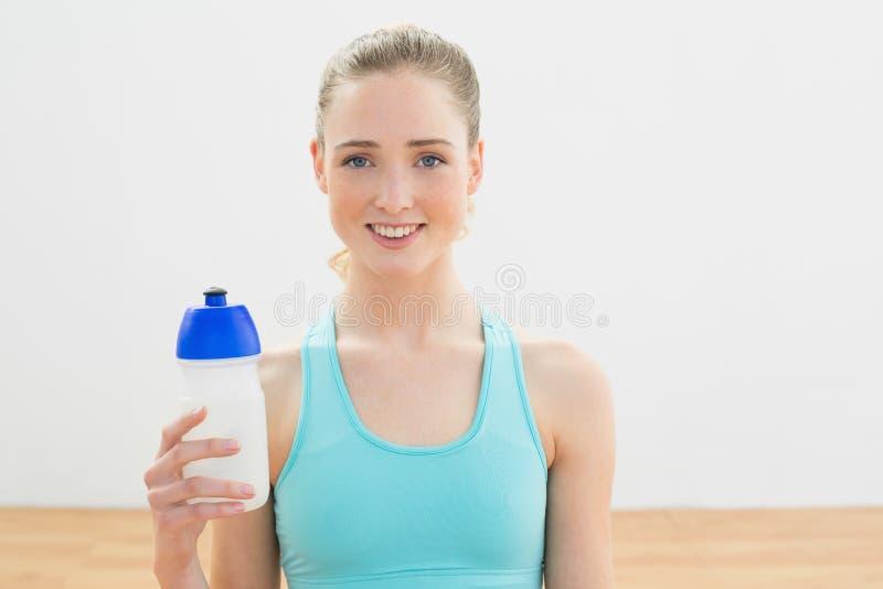La bionda esile sorridente che si siede sulla tenuta del pavimento mette in mostra la bottiglia fotografie stock libere da diritti