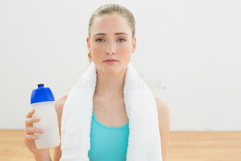 La bionda esile Unsmiling che si siede sulla tenuta del pavimento mette in mostra la bottiglia fotografia stock