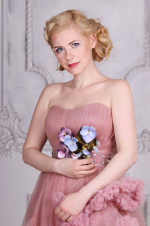 La bionda graziosa in vestito con la pettinatura con i fiori posa fotografie stock libere da diritti