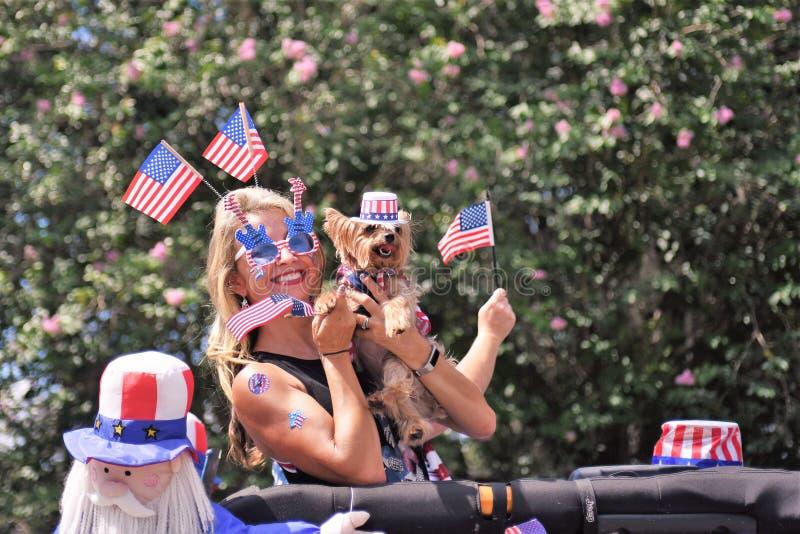 La bionda, l'Yorkshire terrier ed il burattino svegli sono testa coperta da piantare con le bandiere americane immagine stock libera da diritti