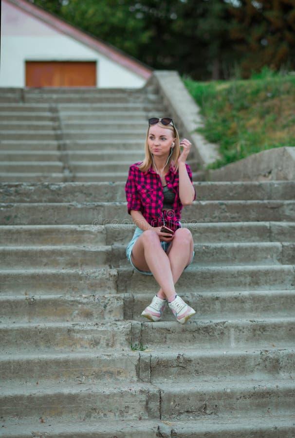 La bionda nel palazzo multipiano blu-chiaro mette, camicia di plaid rossa, scarpe da tennis che si siedono sulle scale fuori Foto immagini stock