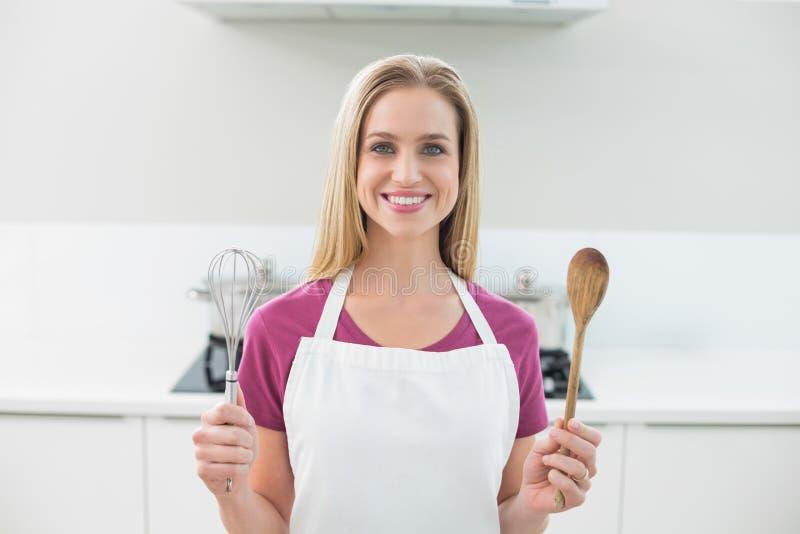 La bionda sorridente casuale che mostra il cucchiaio di legno e sbatte fotografia stock