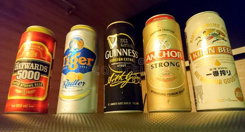 La birra è la birra delle latte delle marche popolari differenti a Singapore fotografia stock libera da diritti