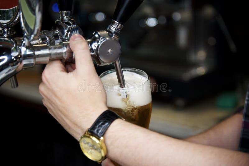 La birra è versata dal rubinetto in un vetro della birra della schiuma fotografia stock libera da diritti