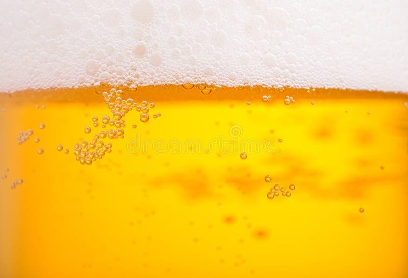 La birra di versamento con la bolla schiuma in vetro per fondo fotografia stock