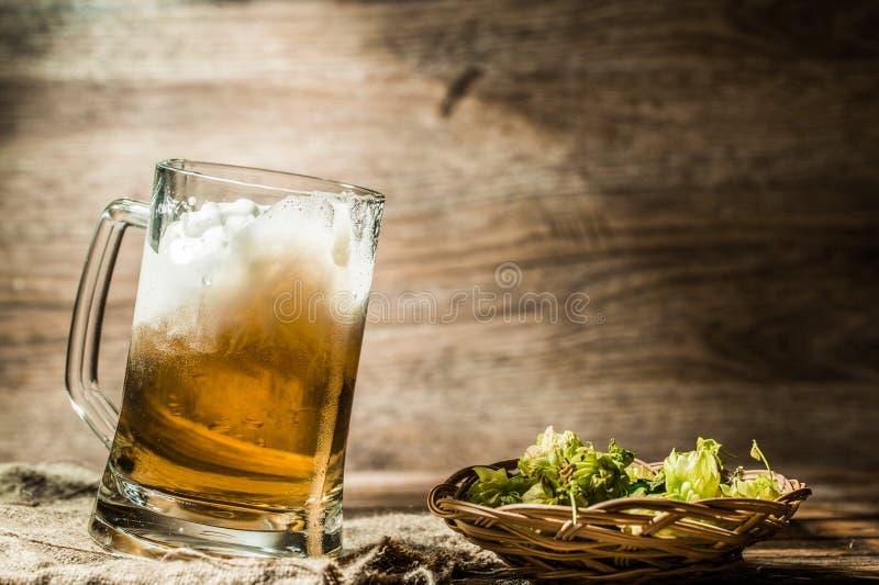La birra spumosa ha versato dalla tazza che sta sul panno di tela fotografia stock libera da diritti