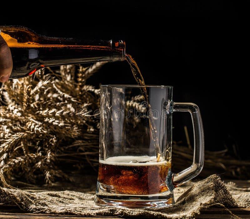 La birra spumosa ha versato nella tazza che sta sul fondo di legno vuoto fotografie stock libere da diritti