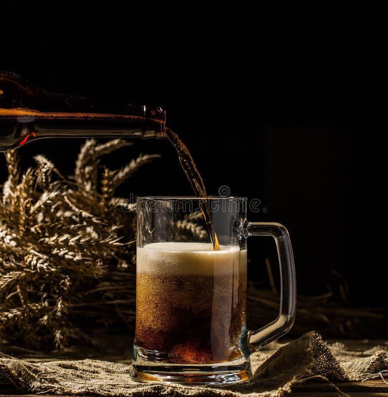 La birra spumosa ha versato nella tazza che sta sul fondo di legno vuoto fotografia stock
