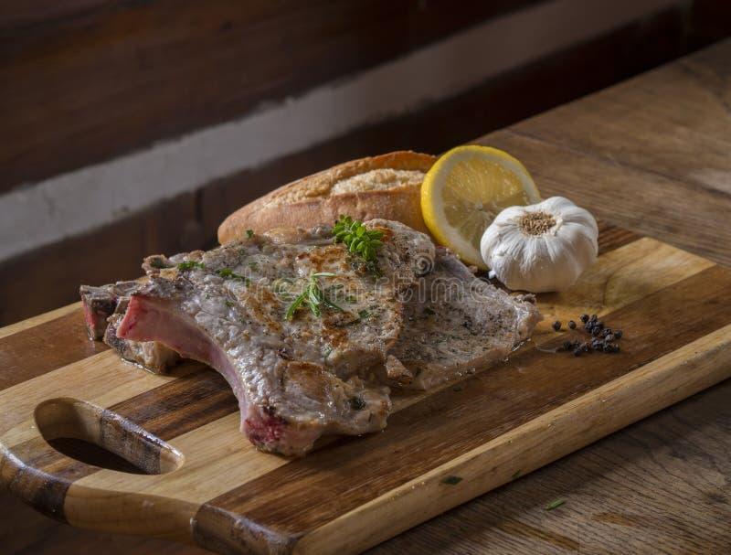 La bistecca arrostita fatta fresca di braciola di maiale con le erbe verdi impana l'aglio immagine stock