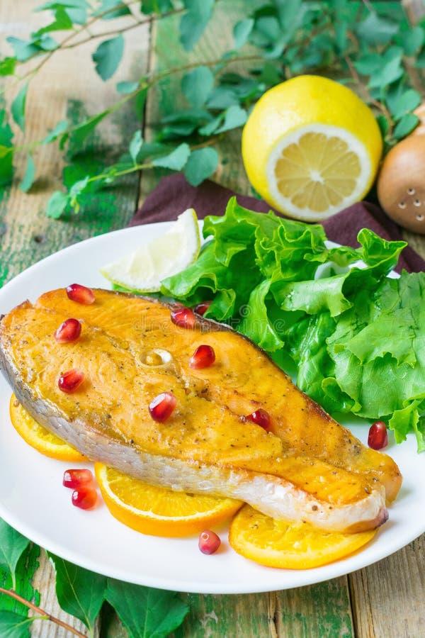 La bistecca di color salmone ha cotto in una marinata delle arance Salmone su un piatto bianco con i semi e la lattuga del melogr immagine stock