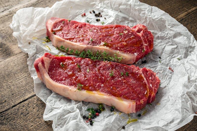La bistecca di controfiletto premio cruda del manzo con il condimento del timo e del cereale e del sale marino del papper ha piov fotografia stock