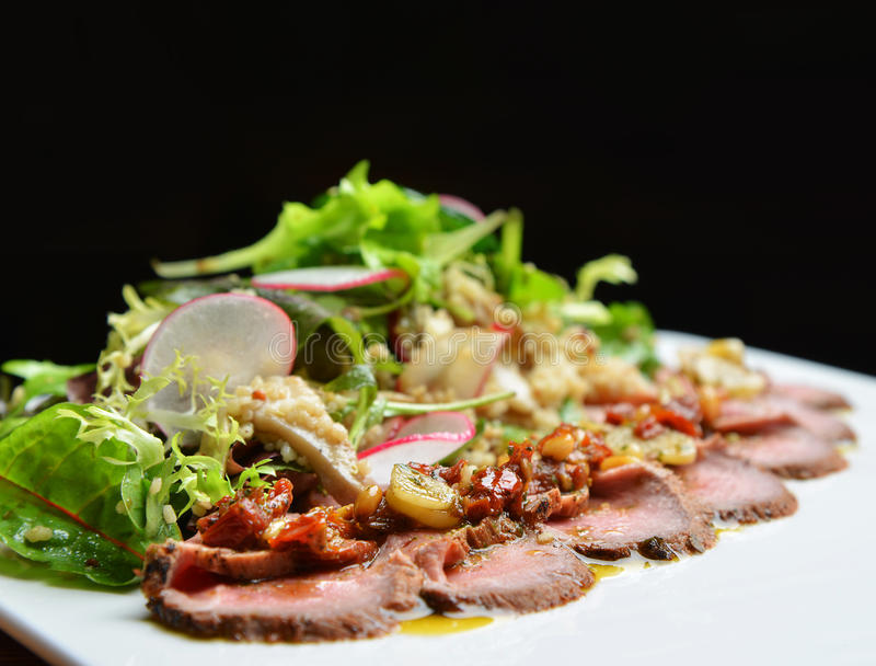 La bistecca di manzo arrostita affettata con l'insalata delle foglie verdi su rustico plat fotografia stock libera da diritti