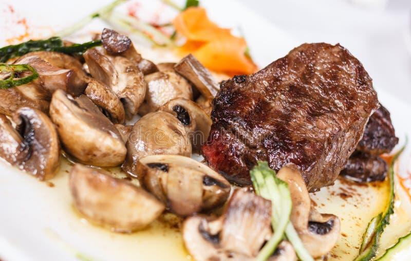 La bistecca di manzo con i funghi saporiti ed il tartufo olio immagine stock