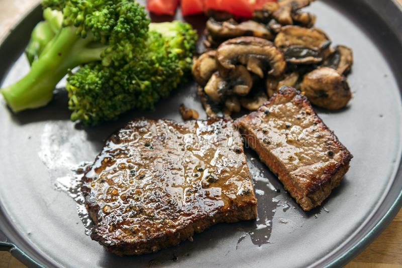 La bistecca di manzo con le verdure gradisce i broccoli, i funghi prataioli ed il pomodoro immagine stock