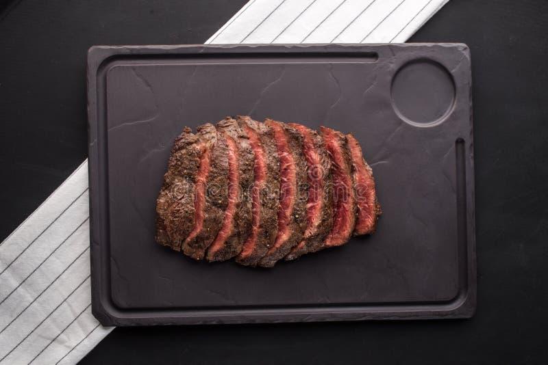 La bistecca di manzo grigliata ha affettato sul bordo di pietra con il tovagliolo bianco su fondo nero fotografia stock libera da diritti