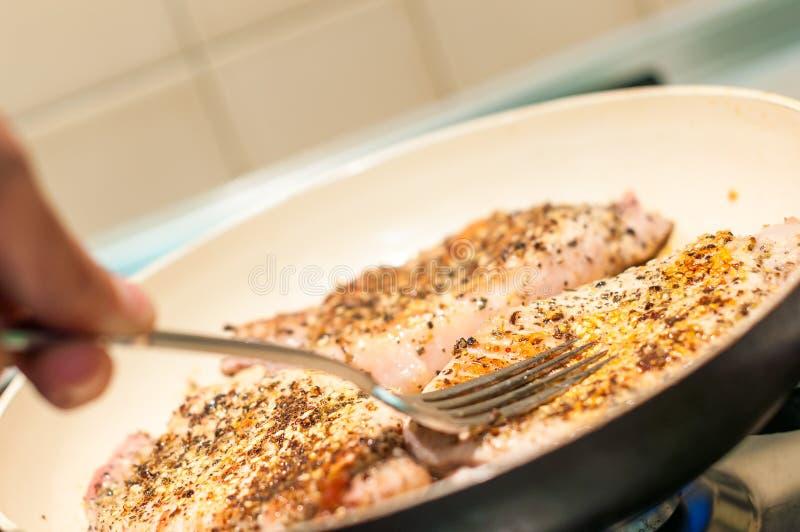 La bistecca di manzo ha fritto in pentola e nella prova con una forcella immagine stock