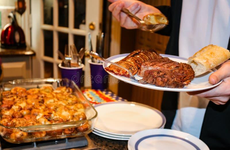 La bistecca e l'aragosta su un piatto hanno tenuto ad un buffet con la mano che tiene un cucchiaio dei funghi farciti dal piatto  fotografie stock libere da diritti
