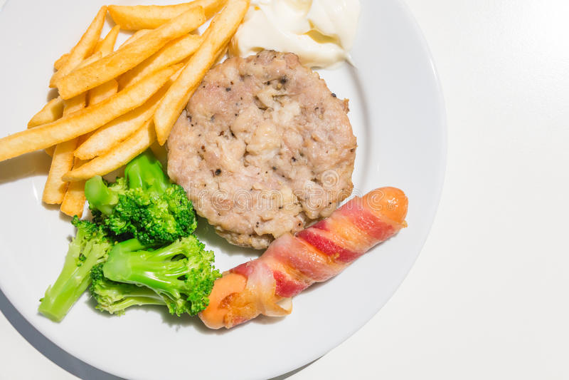 La bistecca, la salsiccia ed il bacon tritati della carne di maiale rotolano con le patate fritte fotografia stock libera da diritti