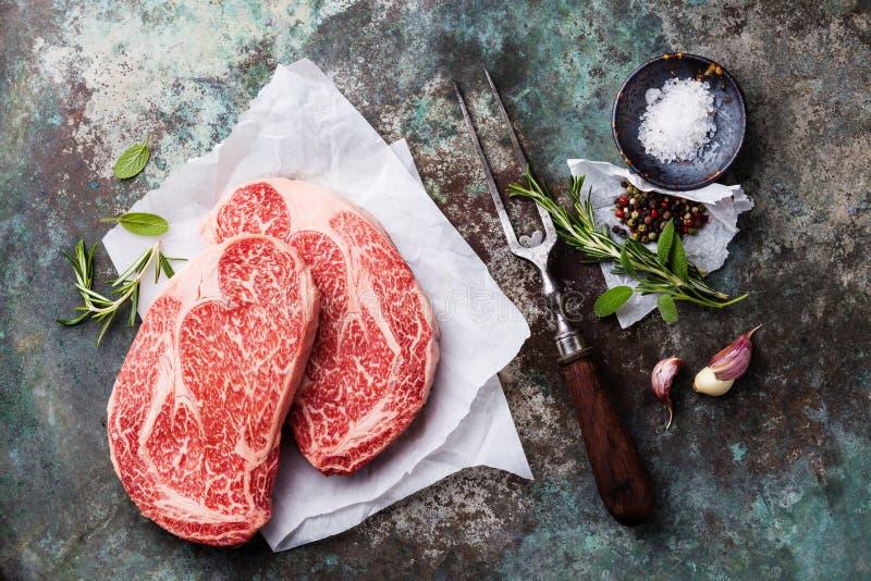 La bistecca marmorizzata cruda Ribeye della carne, i condimenti e la carne si biforcano immagini stock