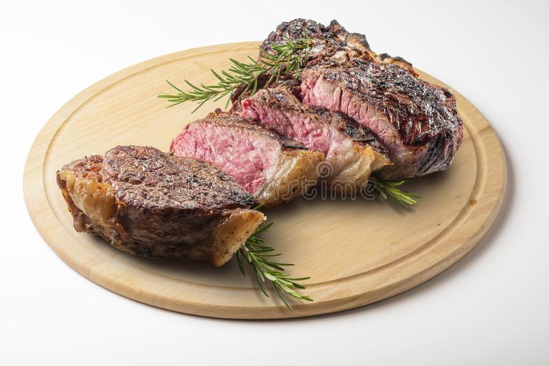 La bistecca nella lombata di Fiorentina ha tagliato sul tagliere di legno rotondo immagini stock libere da diritti