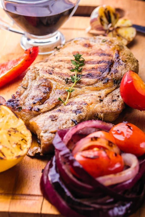 La bistecca succosa della carne di maiale con un ramoscello di timo fresco, limone e verdure arrostite e salsa è servito su un bo fotografie stock libere da diritti