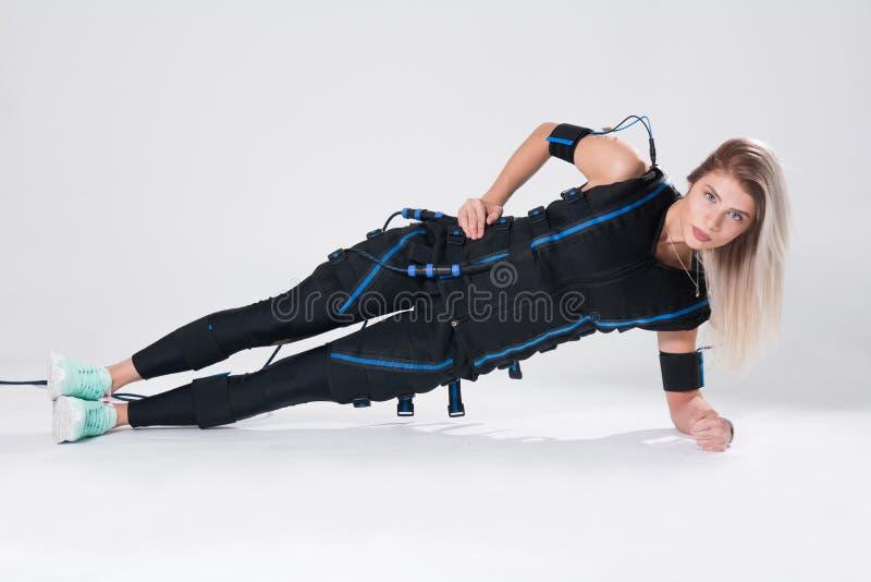 La blonde dans un costume musculaire électrique pour la stimulation fait un exercice sur la couverture photos stock