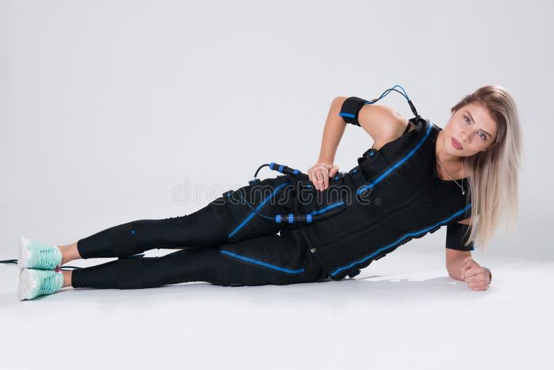 La blonde dans un costume musculaire électrique pour la stimulation fait un exercice sur la couverture photographie stock