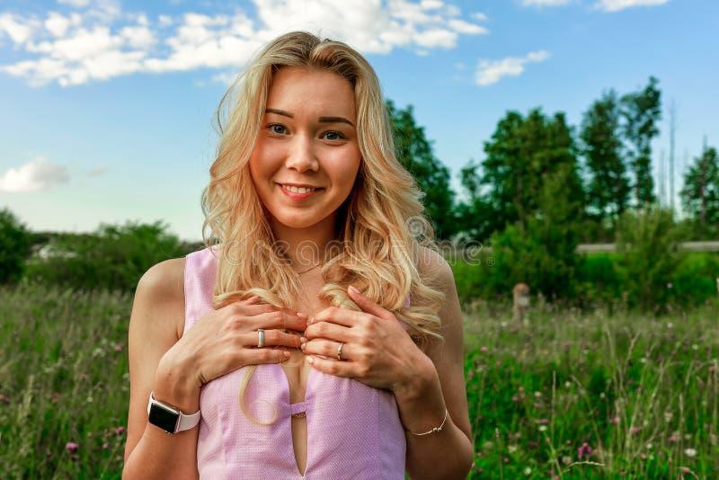 La blonde de ressort en nature avec l'herbe verte avec le décolleté profond couvre son coffre de ses mains photo libre de droits
