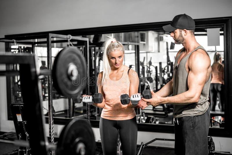 La blonde faisant le biceps courbent l'exercice avec son entraîneur image libre de droits