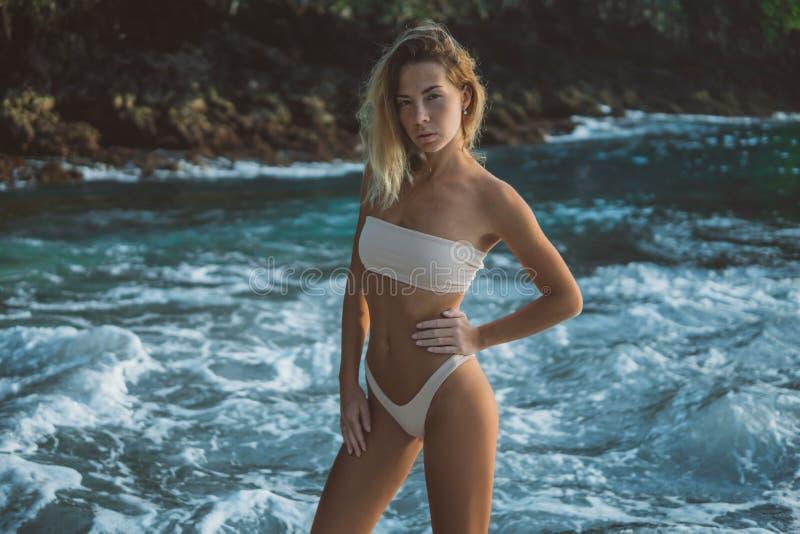 La blonde mince avec des poses de cheveux bouclés sur la plage de l'océan bleu, tient la main sur la taille images stock