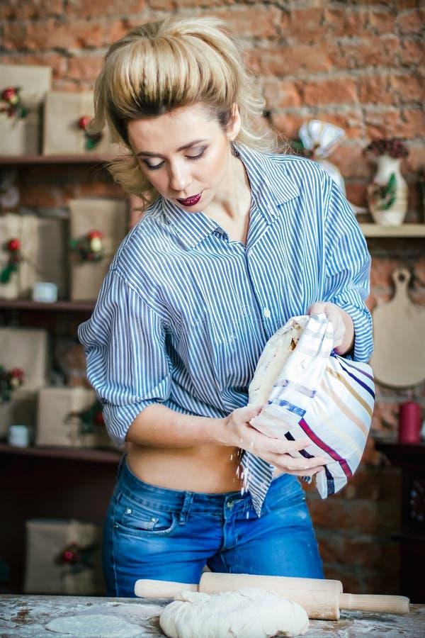 La blonde sexy de jeune femme érotique prépare la pâte dans la cuisine femme au foyer avec des sacs de farine et avec la goupille photographie stock