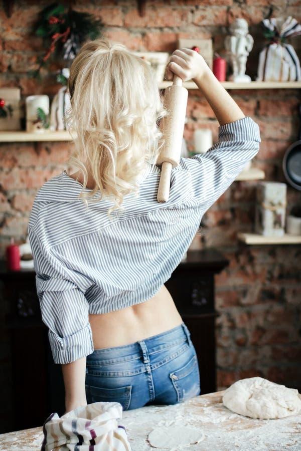 La blonde sexy de jeune femme érotique se tient avec son dos et prépare la pâte dans la cuisine femme au foyer avec des sacs de f photo libre de droits