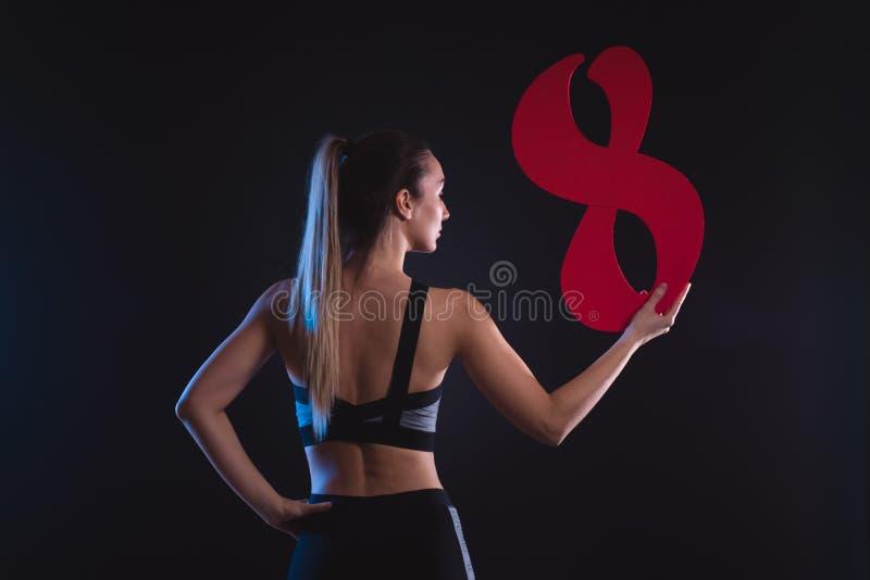 La blonde sportive tient le schéma huit dans les mains photos stock