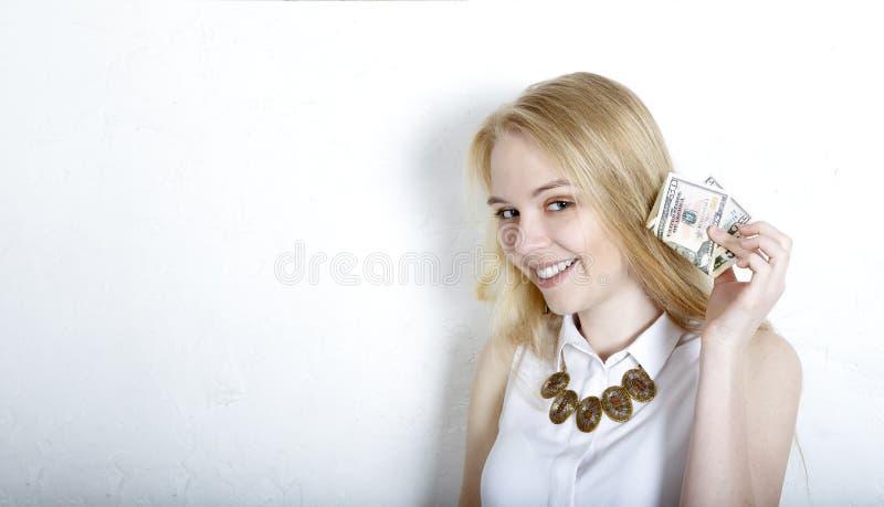 la blonde tient des billets d'un dollar près de son oreille, et écoute avec un sourire satisfaisant le craquement de l'argent End photo libre de droits