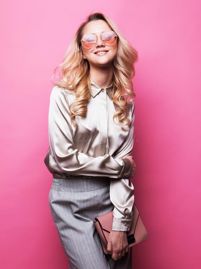 La blusa que lleva, los pantalones y las gafas de sol de la mujer rubia hermosa joven sostiene un bolso imagen de archivo