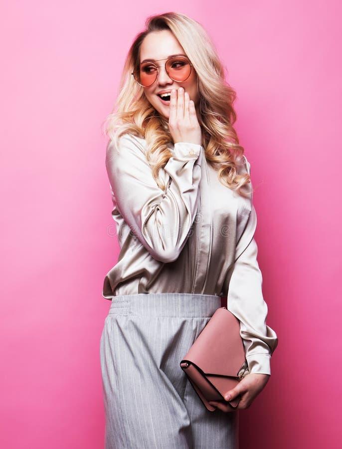 La blusa que lleva, los pantalones y las gafas de sol de la mujer rubia hermosa joven sostiene un bolso imagen de archivo libre de regalías