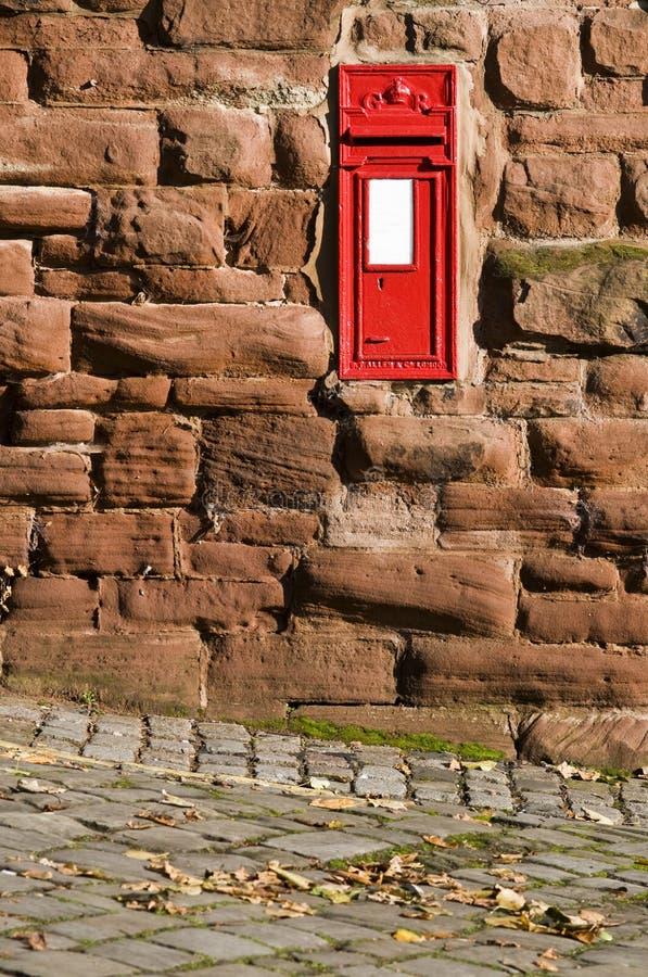 La boîte aux lettres rouge britannique a monté dans le mur en pierre. photos stock
