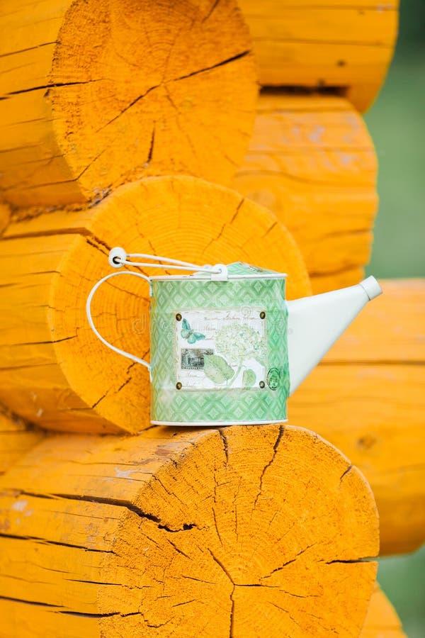 La boîte d'arrosage verte se tient sur un rebord en bois photos stock