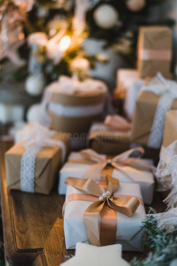 La boîte de cadeaux fabriquée à la main de Noël chic présente avec les arcs bruns Foyer sélectif image stock