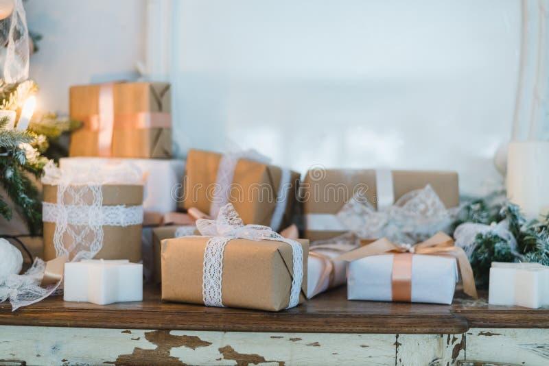 La boîte de cadeaux fabriquée à la main de Noël chic présente avec les arcs bruns Foyer sélectif images stock