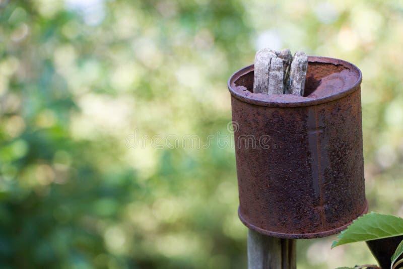 La boîte en fer blanc rouillée accroche sur une vieille barrière en bois au-dessus de la forêt blured, foyer sélectif photographie stock libre de droits