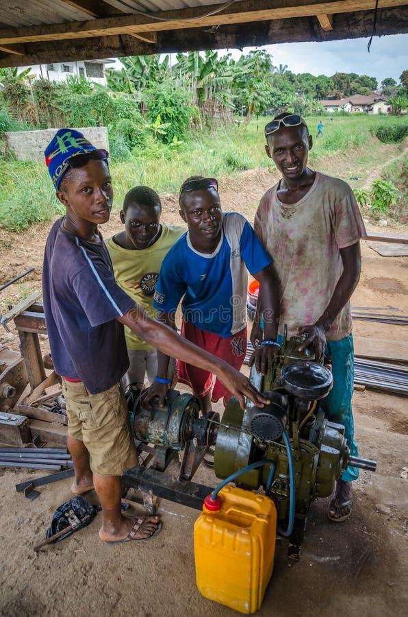 La BO, Sierra Leone - 19 janvier 2014 : Groupe de jeune mécanique africaine non identifiée actionnant le générateur diesel image stock