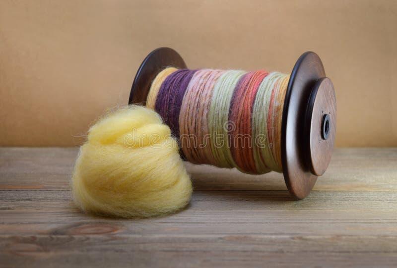 La bobina della ruota di filatura ha riempito di filato della mano fatto della lana degli sheep's con un mucchio di vagabondagg immagini stock libere da diritti